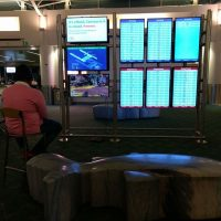 Un usuario conecta su PlayStation 4 a un panel de información de un aeropuerto para jugar a Apex Legends